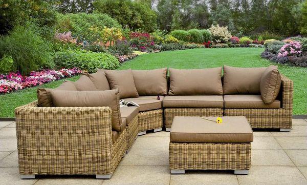 Meble rattanowe: kanapa i stolik w ogrodzie