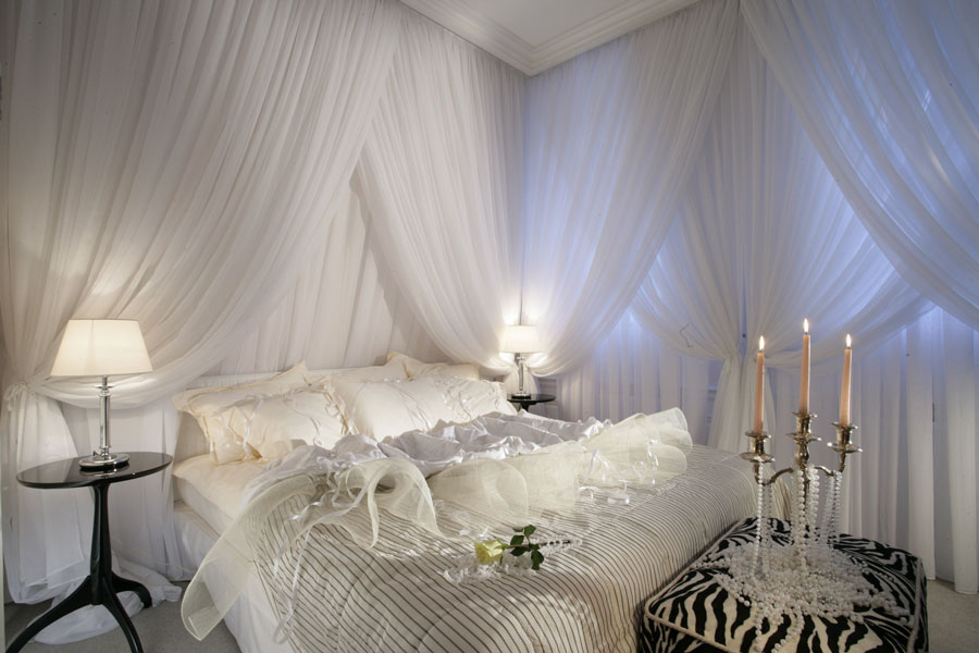 Biała sypialnia w stylu romantycznym, łóżko, firany, lampki nocne, biała róża
