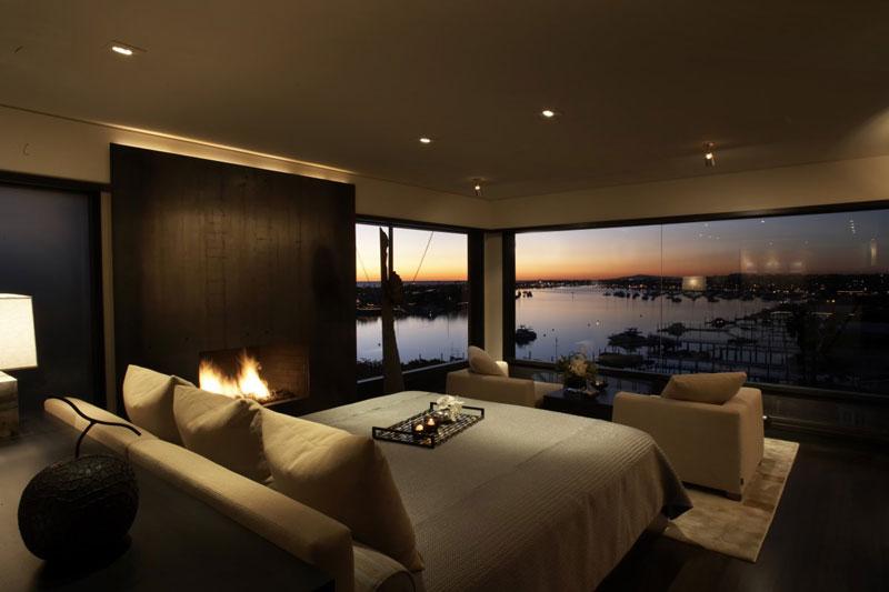 Nowoczesna romantyczna sypialnia z pięknym widokiem i kominkiem. Jasne ciepłe kolory.