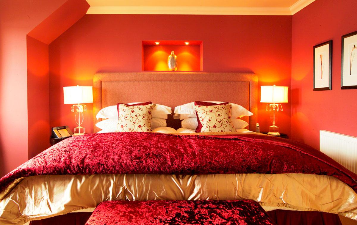 Nowoczesna sypialnia w kolorze czerwonym, z dużym łóżkiem i romantycznym oświetleniem.