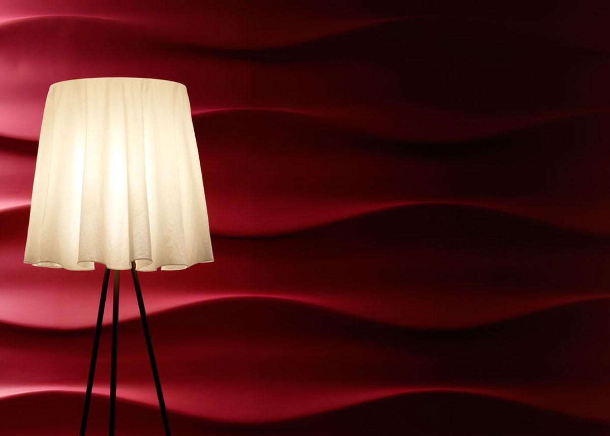 Oświetlony lampą falisty wzór czerwonych paneli 3D rzuca głebokie cienie