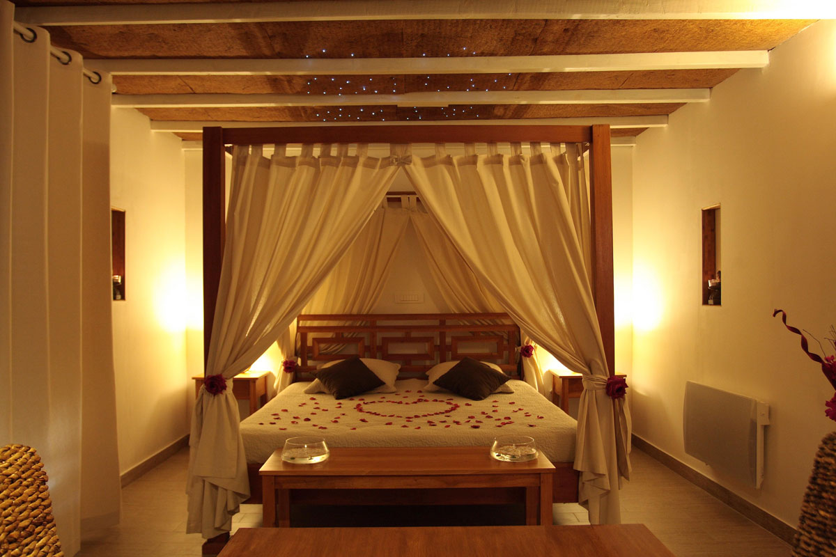 Romantyczna aranżacja małej sypialni dla zakochanych.Na łóżku serce z płatków róży.