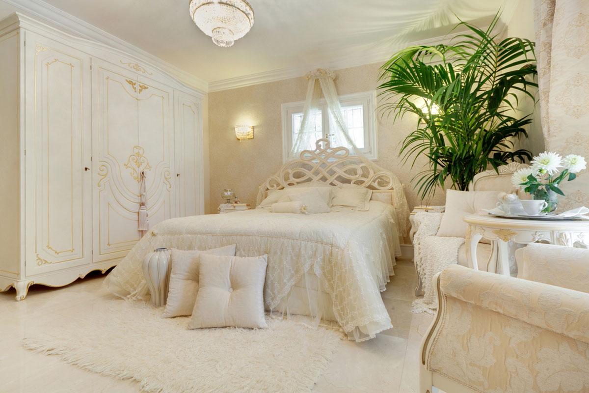 Romantyczna sypialnia w kolorach: kremowy, ecru, zloty. Piękne meble: łóżko, szafa, stolik, fotele.