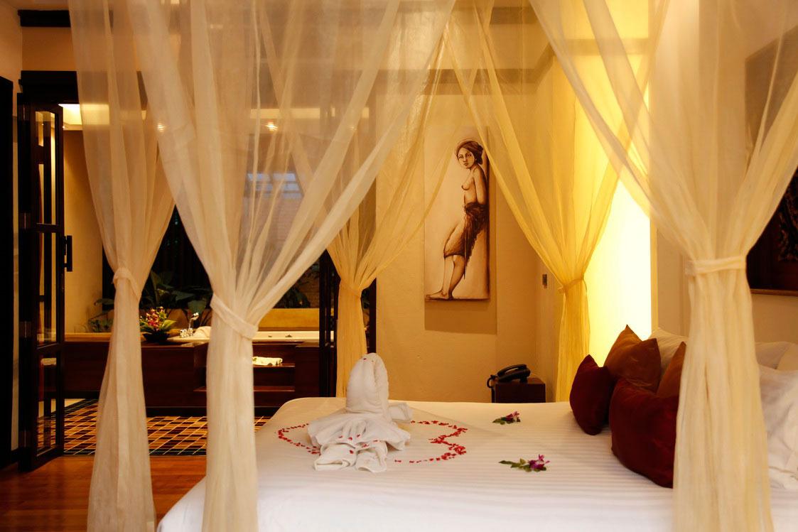 Romantyczna sypialnia na miesiąc miodowy. Ciepłe oświetlenie i łóżko z baldachimem. Serce usypane z płatków róży.