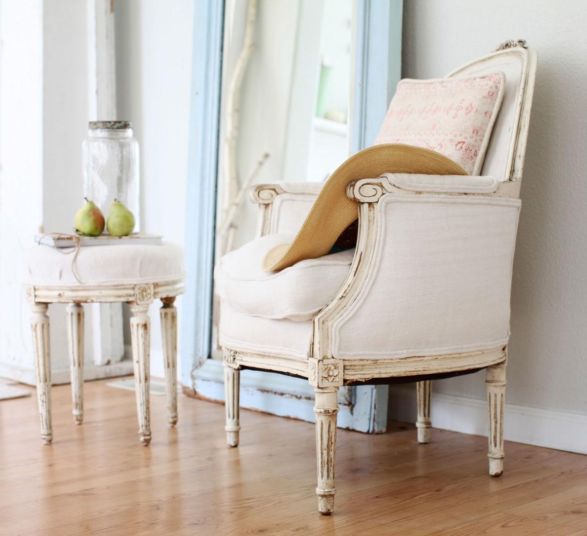 Bielone, stylizowane na antyki meble: krzesło, stołek i lustro z błękitną ramą