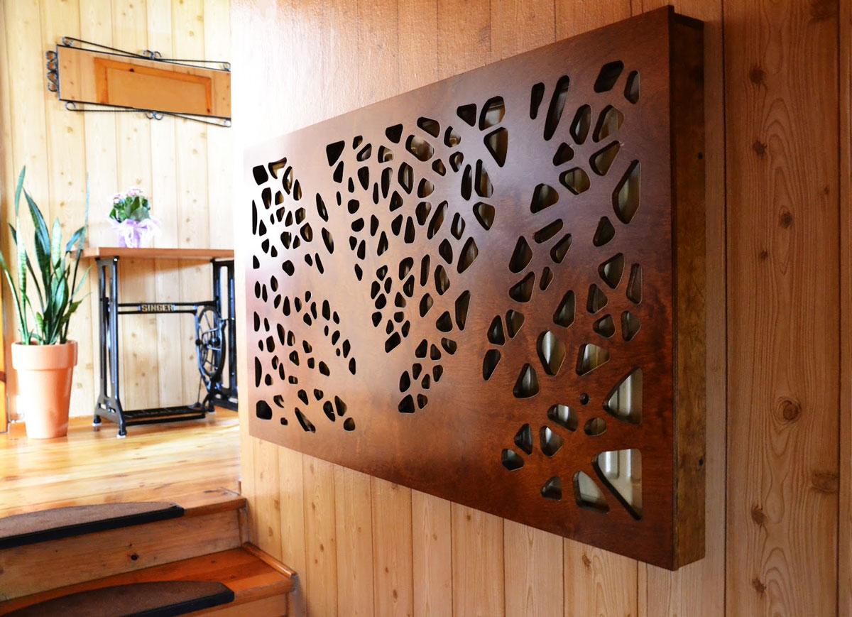 W tej obudowie grzejnika wycięte otwory tworzą wzór drzewa