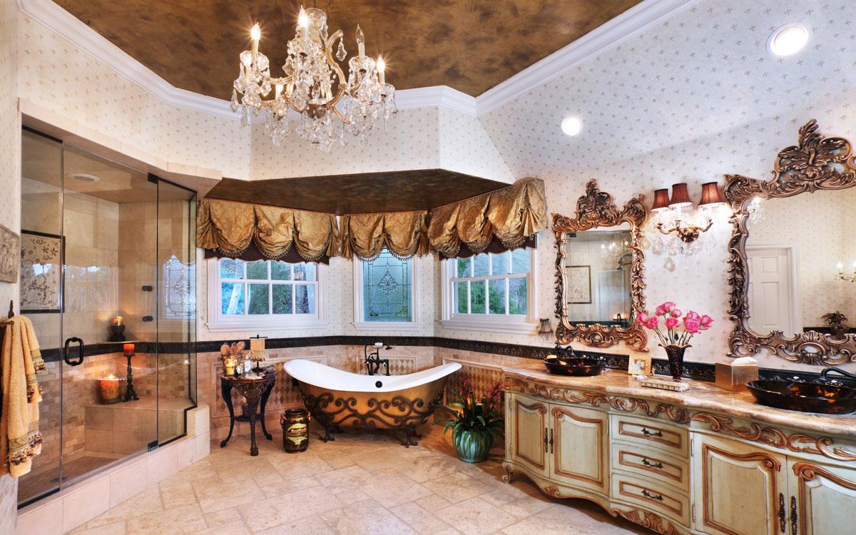 Aranżacja wnętrza dużej luksusowej, ekskluzywnej łazienki. Dominują biel i złoto. Szafki i komoda z długim blatem, ozdobne lustra, zasłony, kinkiet łazienkowy i kryształowy żyrandol.