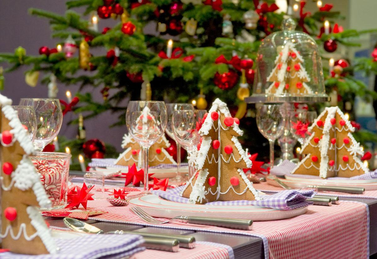 Ciekawe ozdoby świąteczne ręcznie robione: brązowe choinki z piernika i gwiazdki z papieru na stole wigilijnym