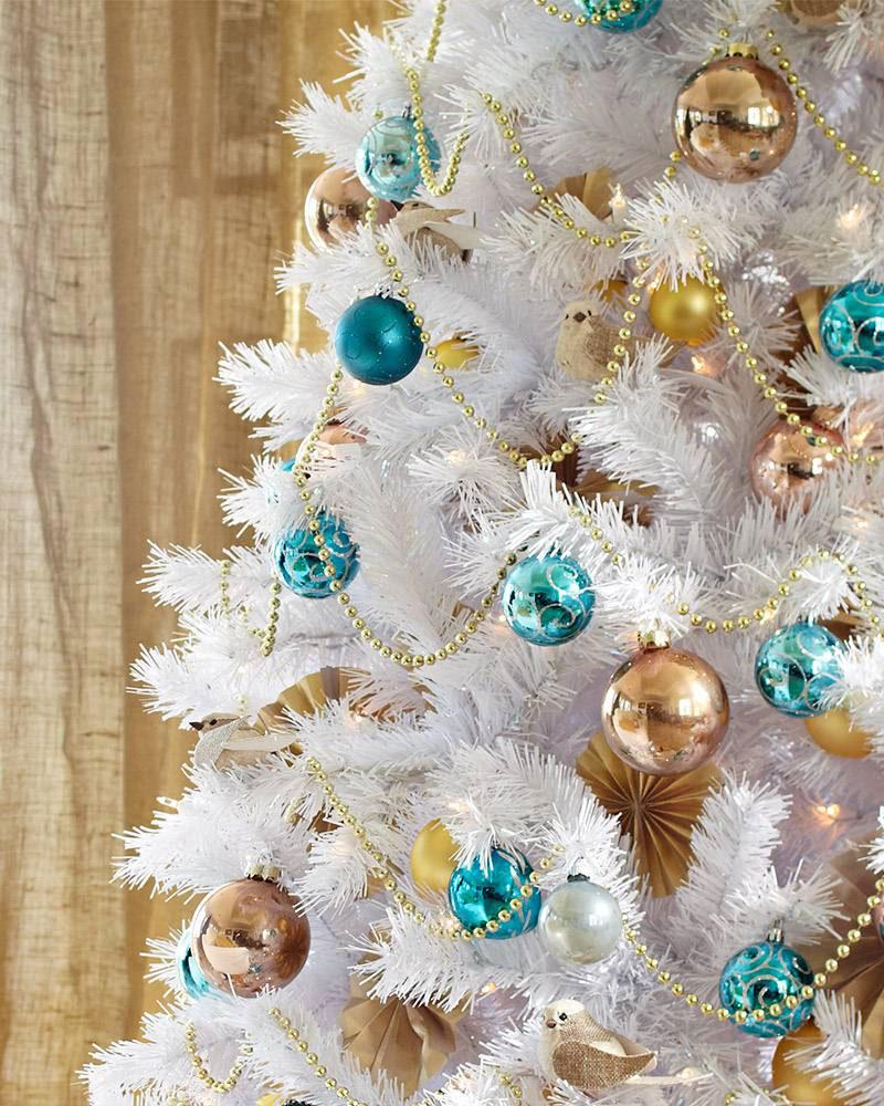 Dwukolorowa dekoracja białej choinki: złote i turkusowe bombki świąteczne