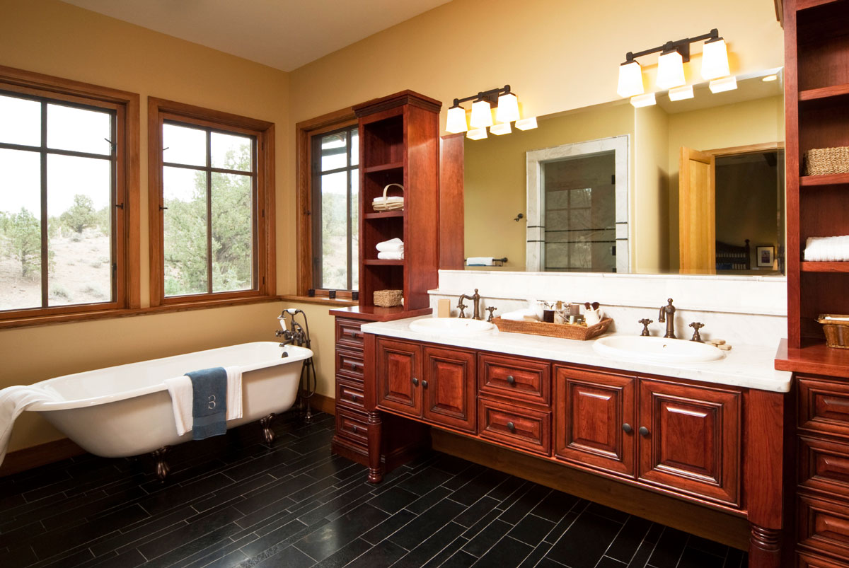 Pomysł na urządzenie wyjątkowej eleganckiej łazienki z białym długim prostokątnym blatem pod dwie umywalki oraz klasycznymi meblami z drewna. Dodatkowe wyposażenie to duże lustro, kinkiety łazienkowe i wanna w stylu retro.