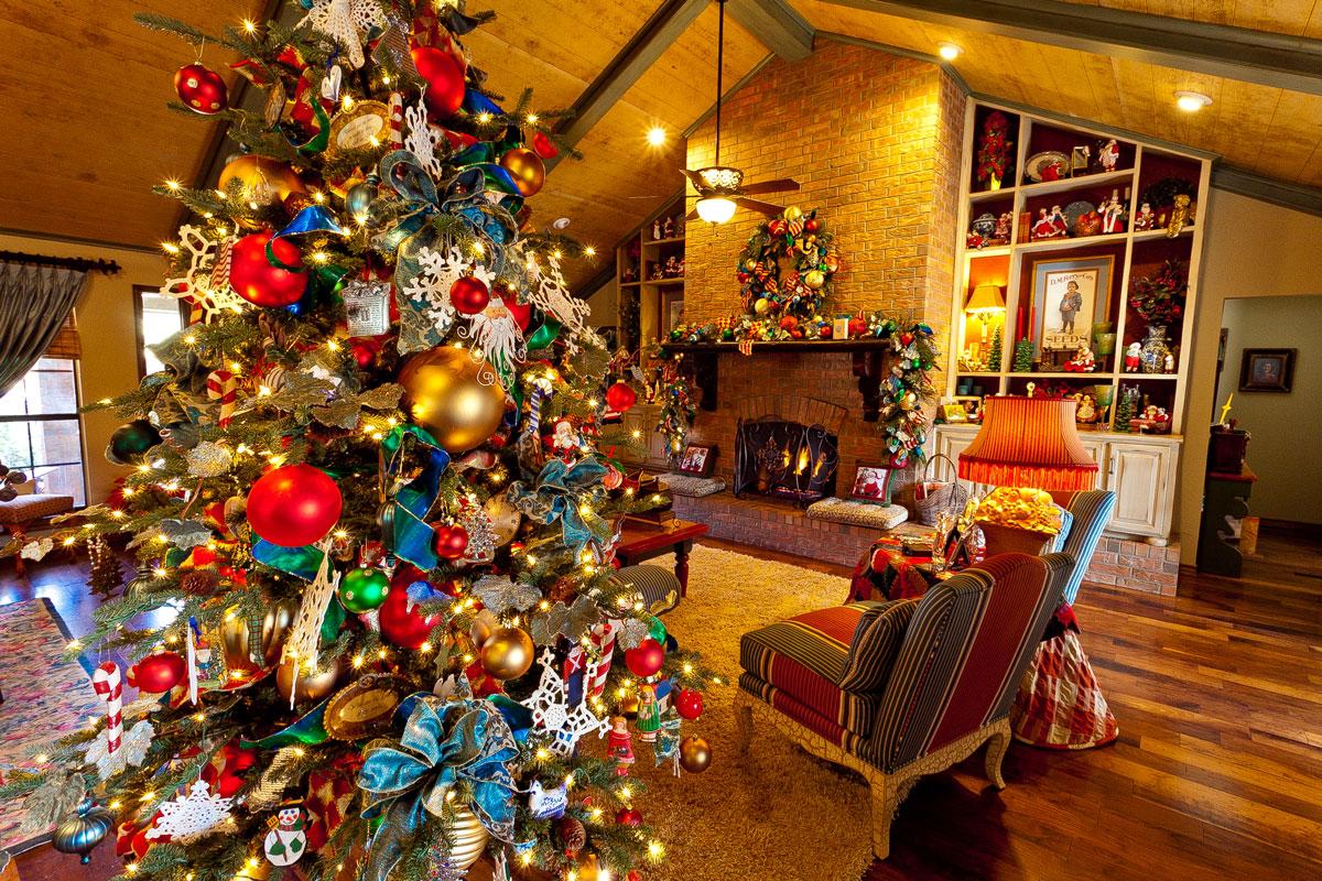 Kolorowa, bogato ustrojona choinka świąteczna udekorowana czerwonymi i złotymi bombkami, niebieskimi wstążkami oraz innymi pomysłowymi ozdobami