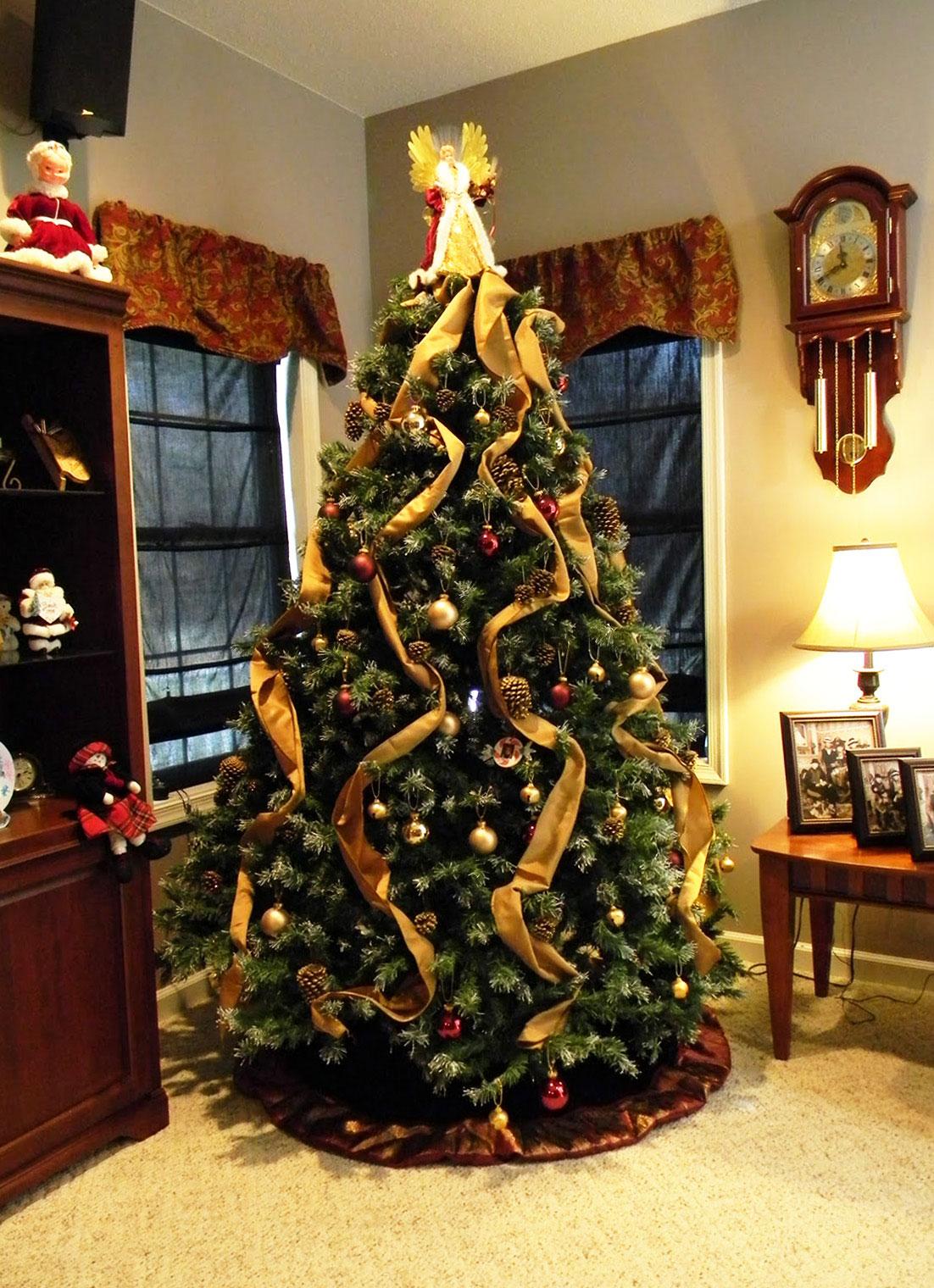 Ładna, gustowna choinka na Boże Narodzenie ozdobiona złotymi szarfami, wstążkami, bombkami oraz świerkowymi szyszkami