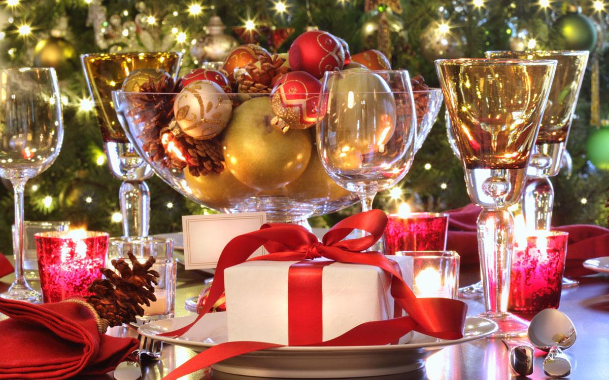Łatwe, własnoręcznie wykonane ozdoby swiąteczne na Boże Narodzenie. Na stole prezent z papieru i czerwonej wstążki oraz półmisek z owocami, bombkami i szyszkami.