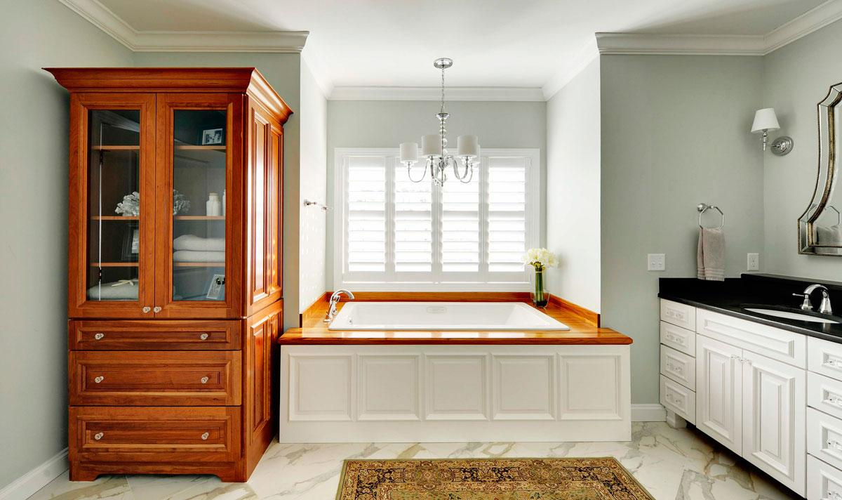 Meble do dużej łazienki z drewnianymi blatami: kwadratowa wanna, narożna oszklona szafa łazienkowa z półkami oraz inne wyposażenie: żyrandol i marmurowe płytki podłogowe