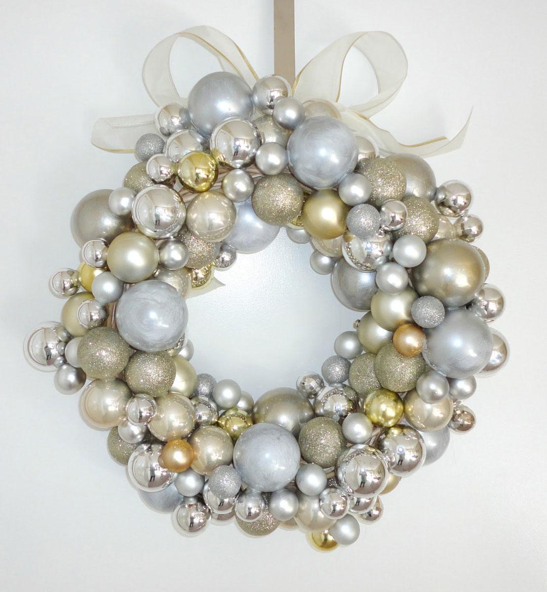 Okrągła srebrno-złota świąteczna ozdoba z koralików i bombek. Do zawieszenia na oknie lub drzwiach.