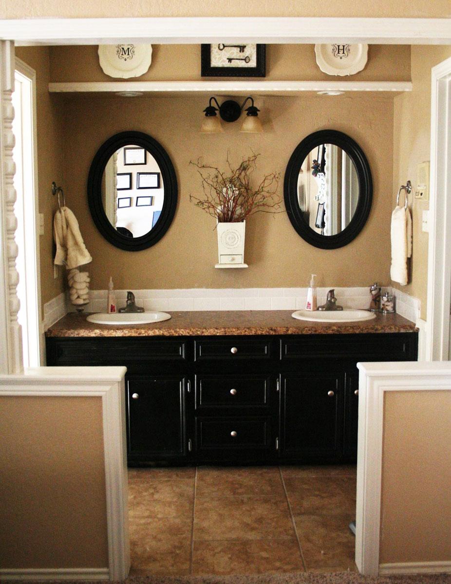 Pomysł na meble do małej łazienki: ciemno-brązowe drewniane szafki łazienkowe z umywalkami wpuszczanymi w blat, owalne lustra z drewnianą ramą, oświetlenie punktowe sufitowe i kinkiety