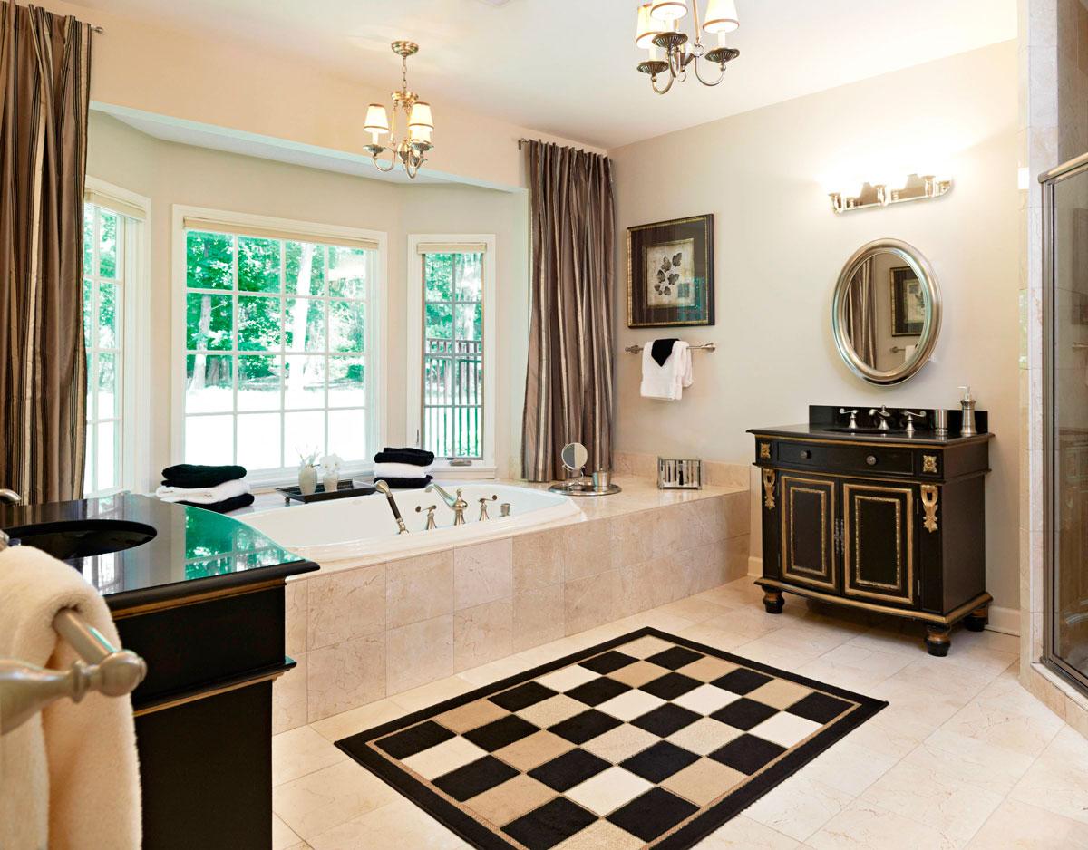 Projekt wnętrza dużej łazienki w biało-czarno-brązowej kolorystyce ze złotymi ozdobami. Luksusowa wanna, królewskie szafki umywalkowe, owalne lustro i dywanik w szachownicę.