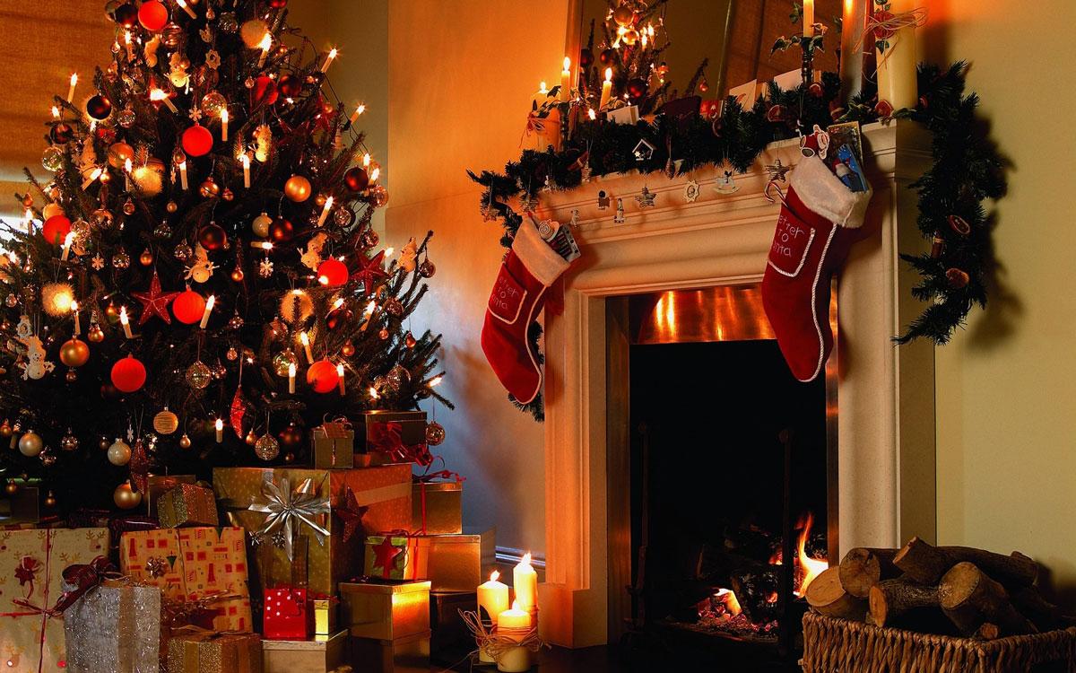 Świąteczna aranżacja: oświetlenie i ozdoby choinkowe oraz udekorowany gałązkami i świecami kominek. Dodatkowo świąteczne skarpety na prezenty.