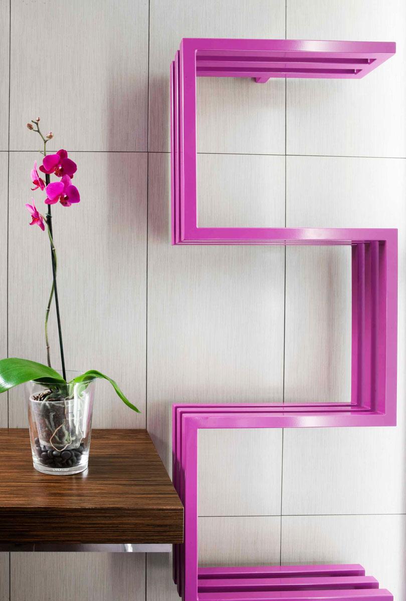 Prosty różowy grzejnik łamany pod kątem prostym obok różowego storczyka w przeźroczystej doniczce