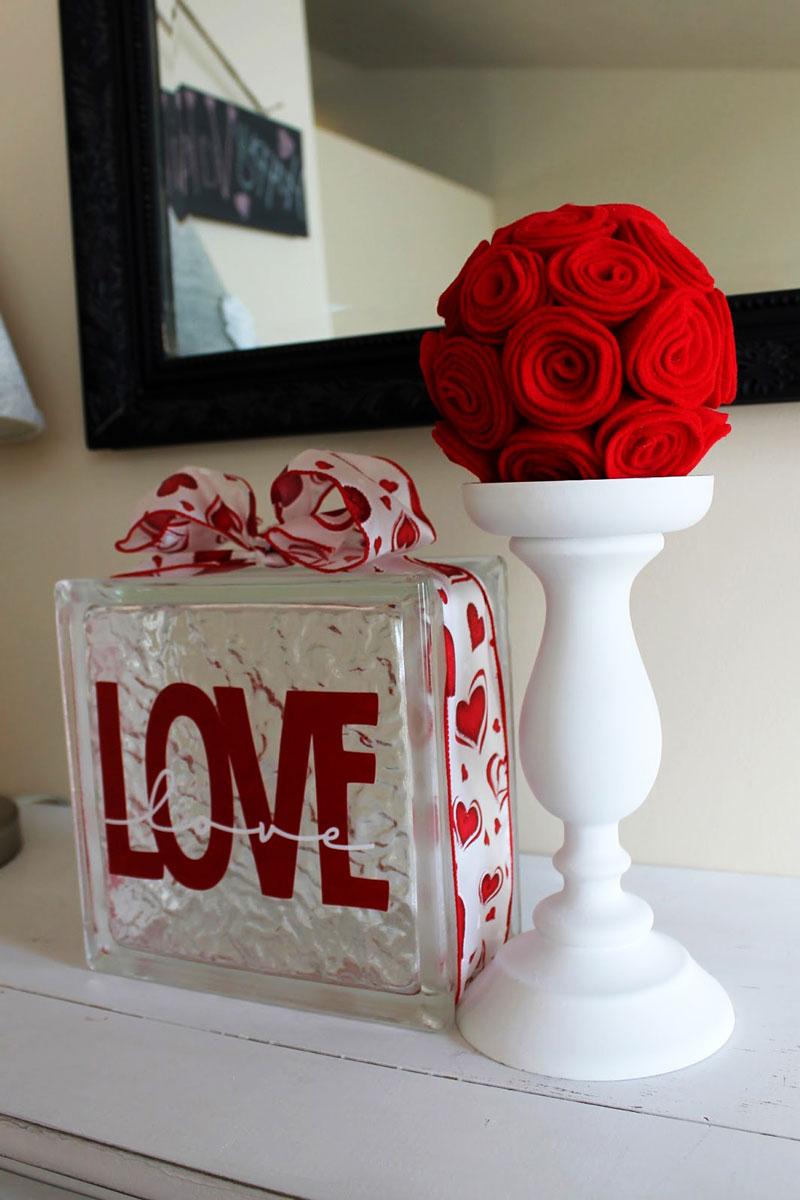 Dekoracje walentynkowe można zrobić ze wszystkiego: przystrojony wstążką szklany luksfer i filcowe, czerwone róże