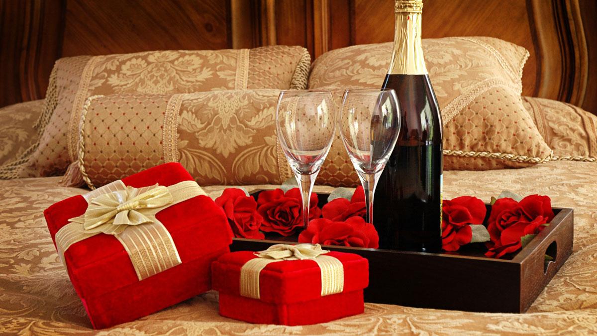 Niespodzianka dla ukochanej osoby: romantyczny wystrój sypialni na Walentynki z różami, prezentami i szampanem na łóżku