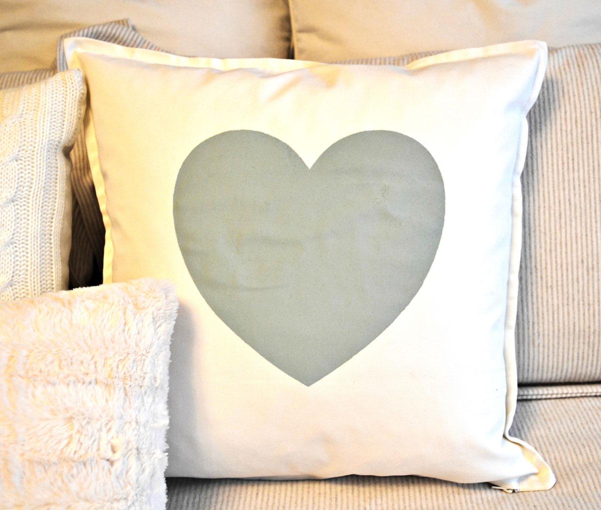 Oryginalny prezent lub dekoracja na Walentynki, którą możesz zrobić sama: biała poduszka ozdobna z naszytym szarym sercem - na sypialnianym łóżku