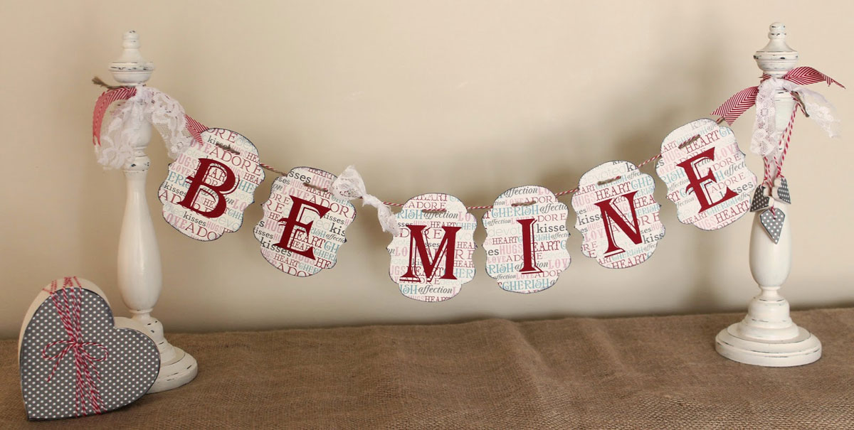 Prosty pomysł jak zrobić dekoracje na Walentynki DIY: wstążki, karteczki z napisem i bombonierka z czekoladkami
