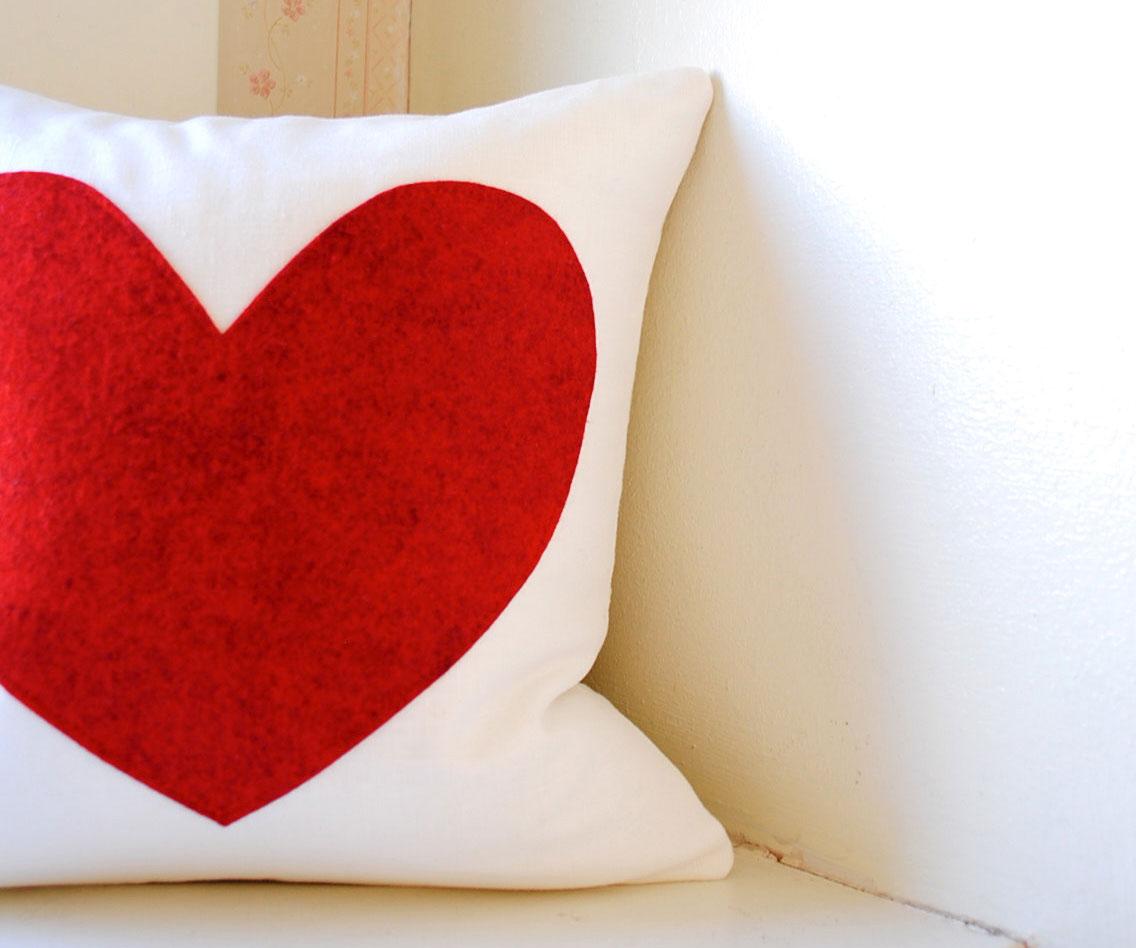 Ręcznie robiona, biała poduszka dekoracyjna z czerwonym sercem naszytym na poszewkę - sprawdzi się jako ozdoba lub prezent