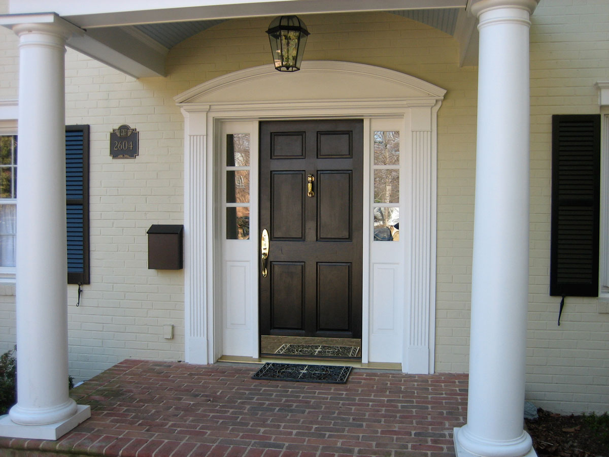 Zewnętrzne drzwi wejściowe do domu: drewniane, w ciemno-brązowym kolorze, ze złotą klamką i szyldem, na werandzie z dwiema białymi kolumnami