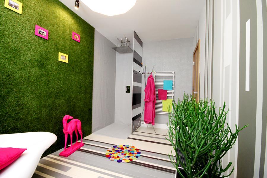Dekoracyjna syntetyczna sztuczna trawa wraz z obrazkami na ścianie w łazience