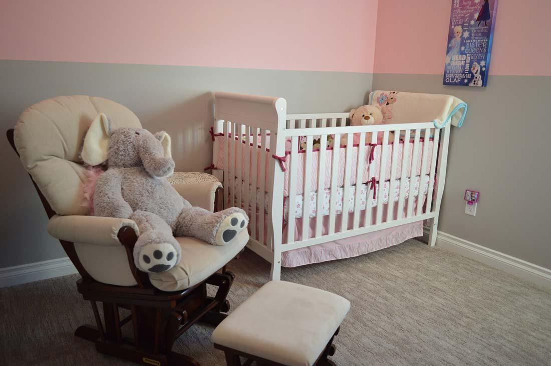Pokój dzieciecy w kolorach białym i rózowym: łóżeczko dla dziecka, fotel i miś